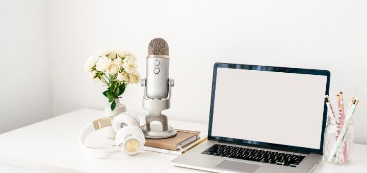 Image with laptop, headphones and microphone on the desk. - The top blogging tools and resources for bloggers in my toolkit.